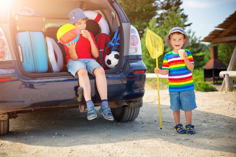 Crianças perto do carro a fazer uma pausa na viagem de carro para as férias